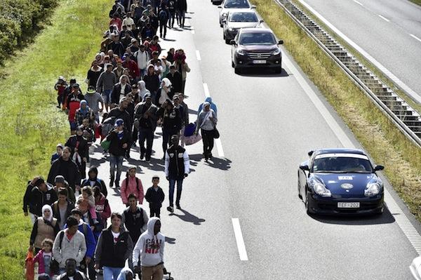 En stor gruppe flygtninge og migranter, der søndag aften ankom til Rødby på Lolland, er mandag den 7. september 2015 begyndt at gå mod nord - angiveligt med et ønske om at søge asyl i Sverige. (Foto: Bax Lindhardt/Scanpix 2015)